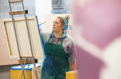 A student working on a canvas in the art studios.