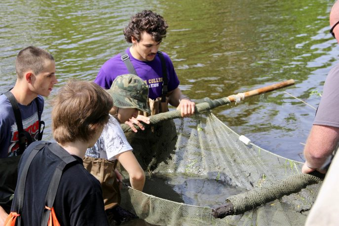 Group of Albion College community members holding a net while standing in a river