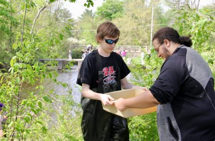 Two Albion College community members working outside by a river holding a tub of water