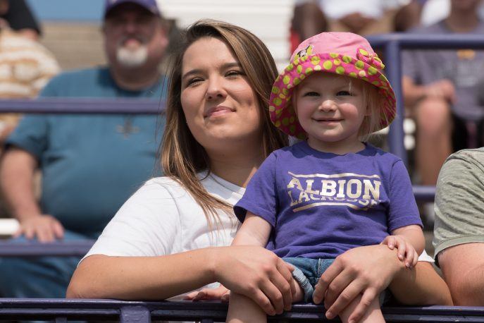 Child in the bleachers in an Albion Lacrosse shirt.