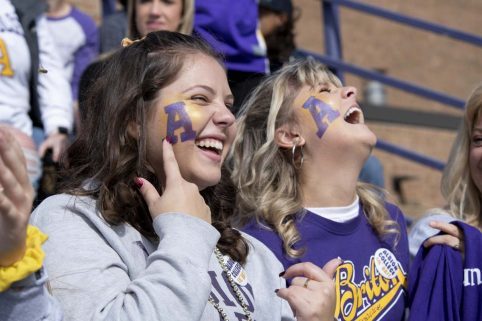Two Albion College students in the bleachers with their faces painted.