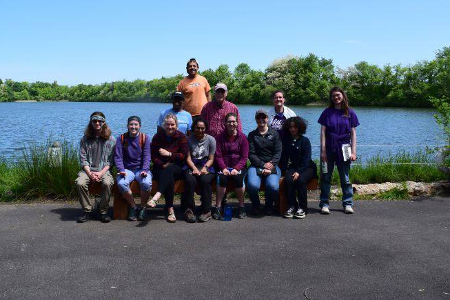 Group of students and faculty outside in front of a blue body of water.