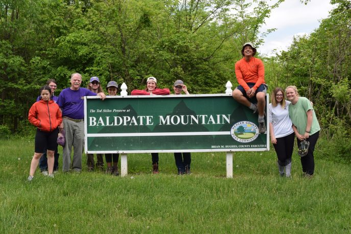 "Group of students and faculty member posed with a sign reading ""Baldplate Mountain""."