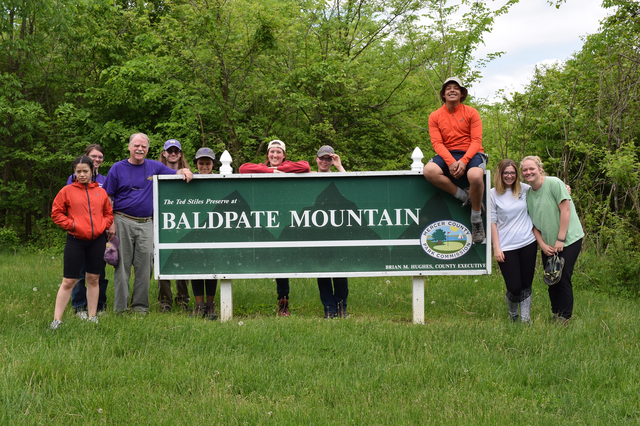 """Group of students and faculty member posed with a sign reading """"Baldplate Mountain""""."""