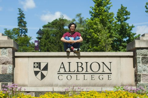 Anh Dinh posing on the Albion College campus sign