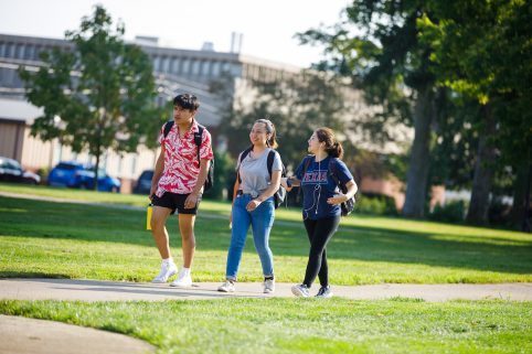 Three students walking outside on campus.