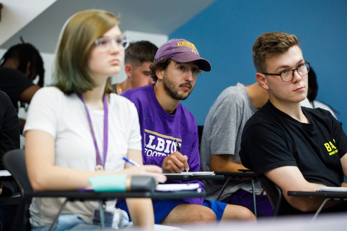 Three students sitting in class, looking ahead to the professor.