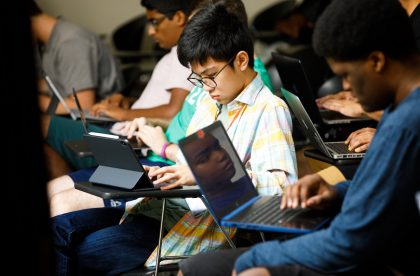 Students working on laptop computers in a classroom setting.