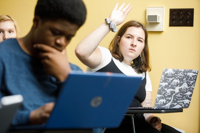 A student raising her hand in class.