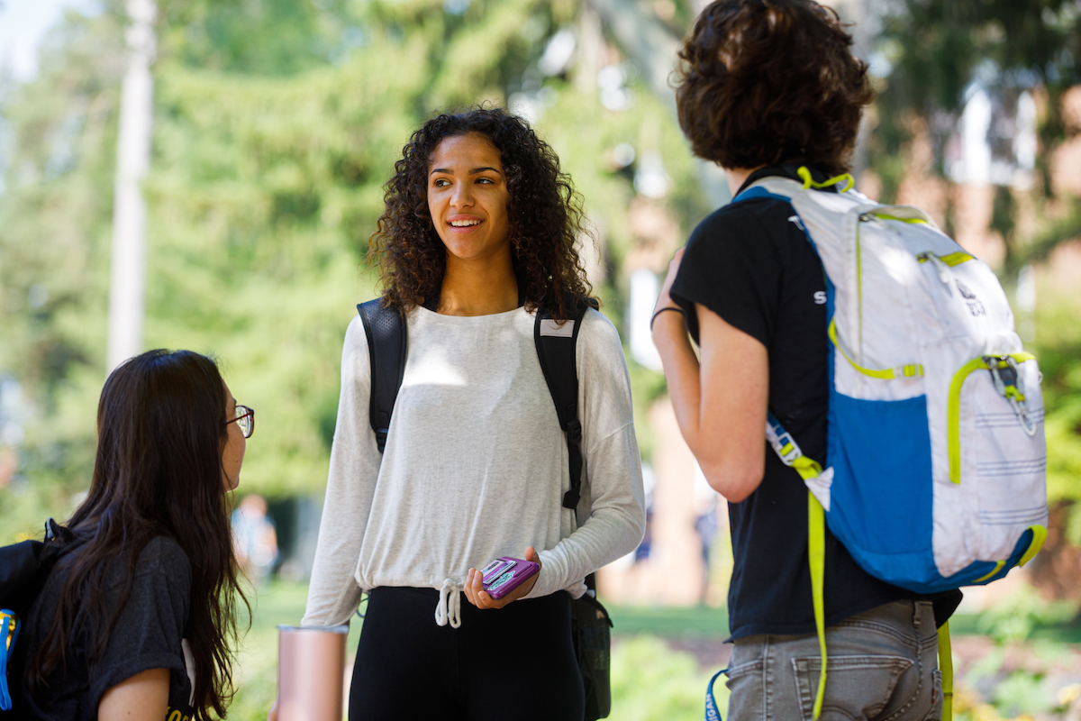 Students outside conversing on campus.