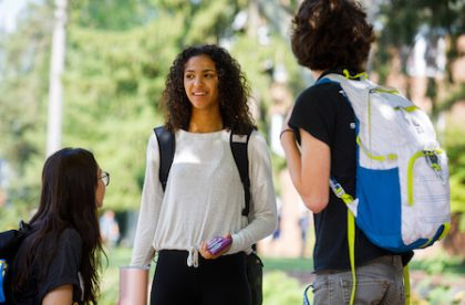 Three Albion College students talking outside on campus