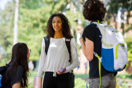 Three Albin College students talking outside on campus