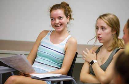 Students in a classroom taking part in a classroom discussion