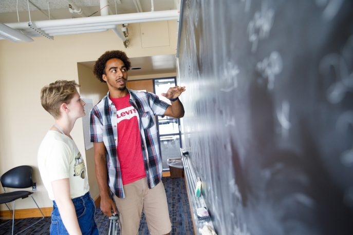 Two Albion students discussing writing on chalkboard.