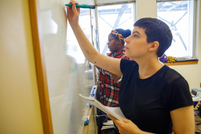 Two students working together and writing on a whiteboard