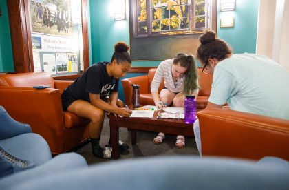 Three Albion College students working together in a common area on campus