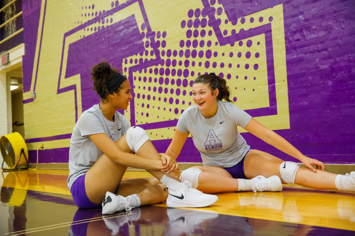 Two students sitting on the volleyball court in Kresge.