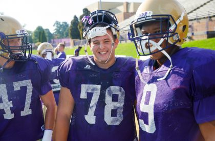 Three Albion College football players on the field.