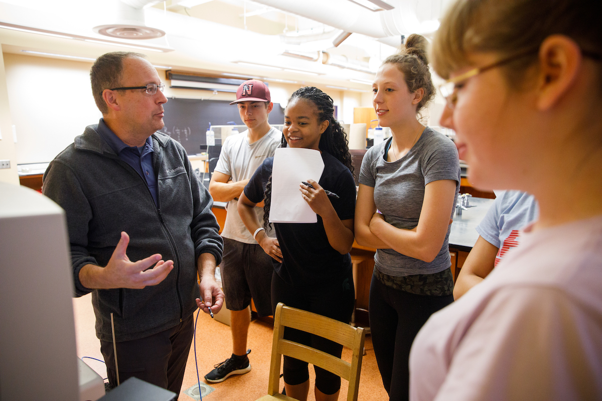 Faculty member conversing with a group of students in a classroom setting.