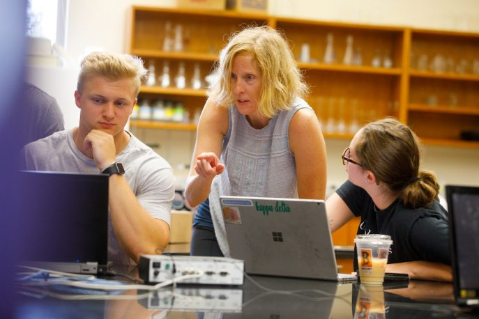 Faculty member working with students in a lab