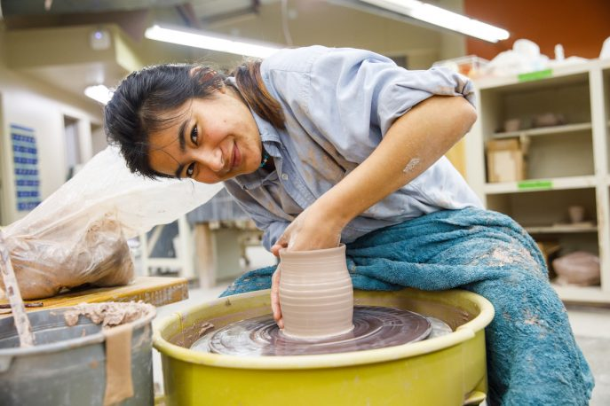 Student throwing pottery on a wheel in an art studio
