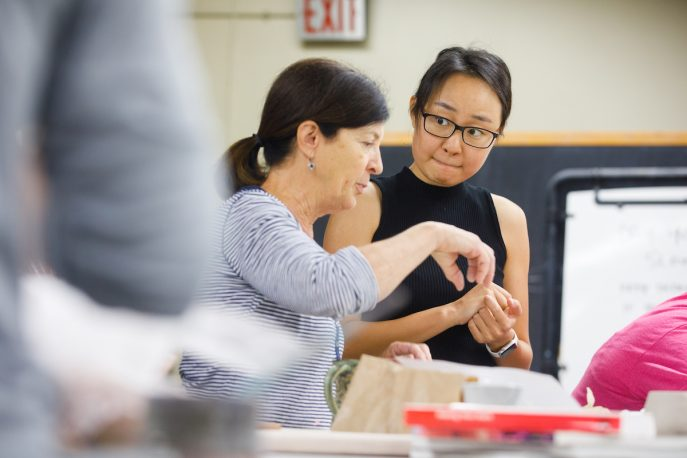 Faculty member converses with student in a pottery studio.