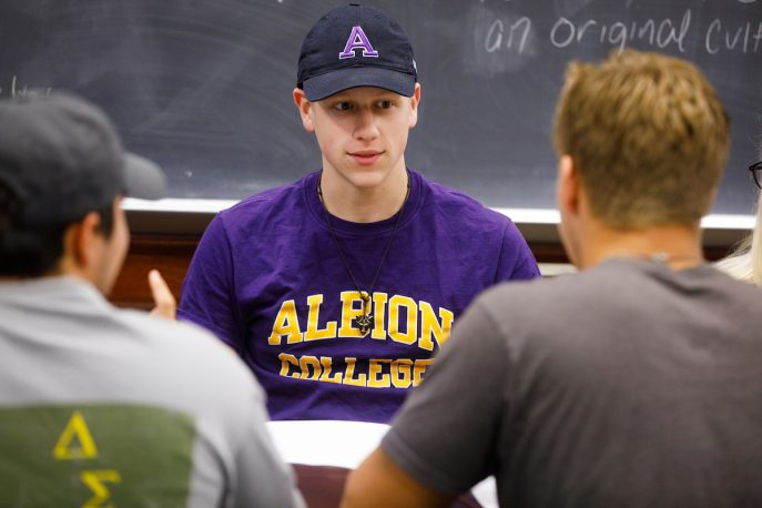 Albion College students conversing in a classroom setting.