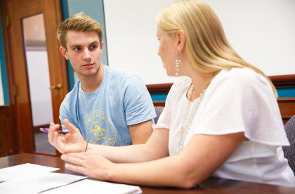Student conversing with a faculty member in a classroom setting.