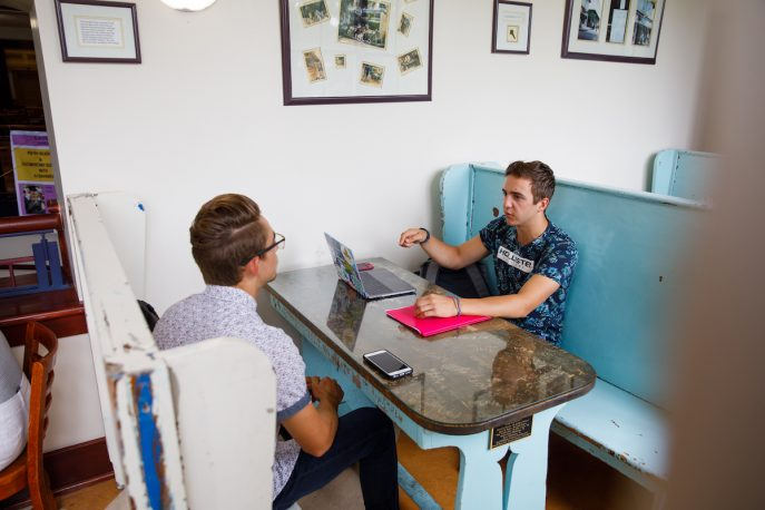 Two students conversing at a table.