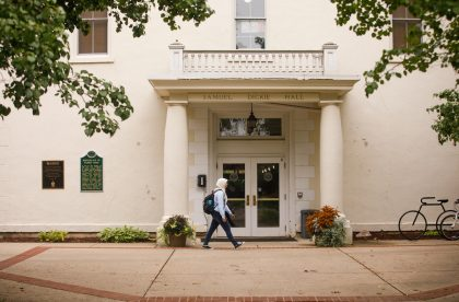 Student walking in front of Samuel Dickie Hall.