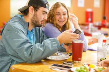 Two students enjoying a meal together in the dining hall