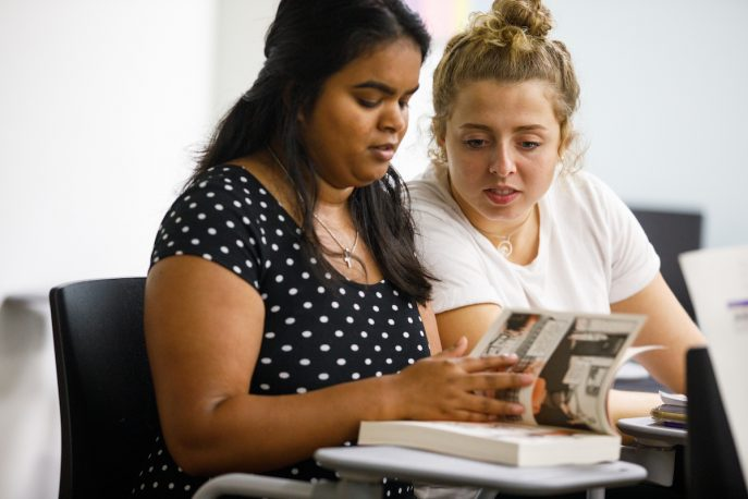 Two students sitting together reading a book together