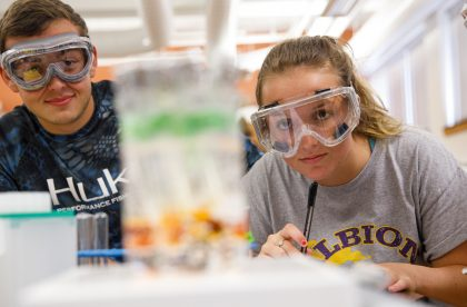 Two Albion students wearing protective goggles in a lab setting.