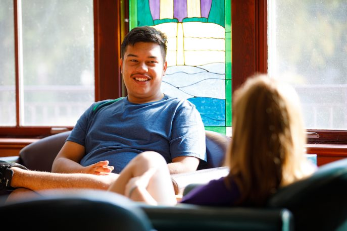 Two students talking in a common area on campus