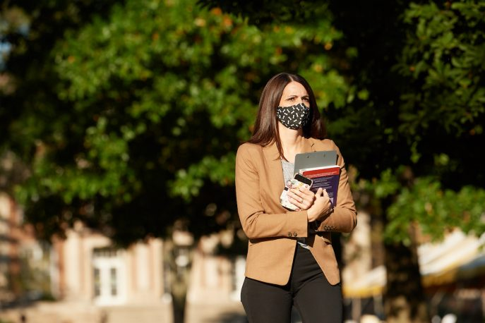Woman wearing a mask walking on campus.