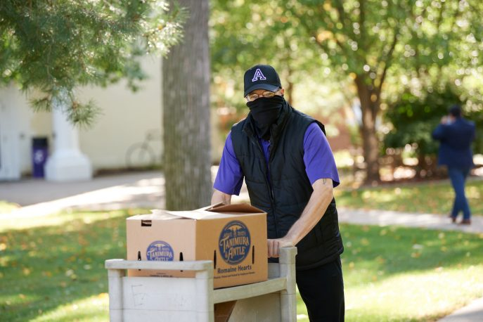 Albion College staff member wearing a mask on campus.