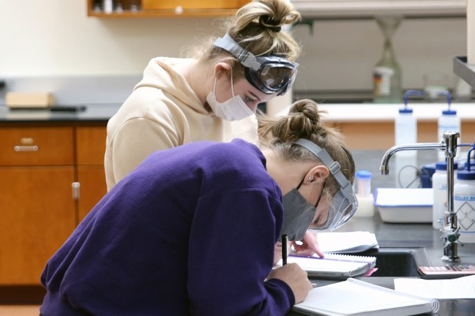 Two students in masks and goggles working in a lab