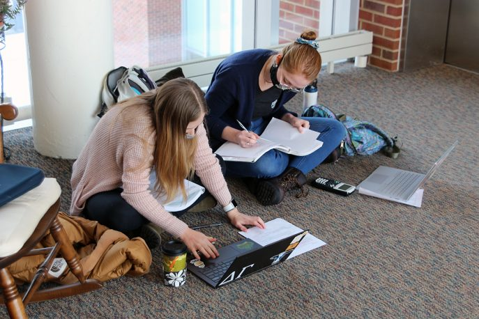 Two students wearing masks working on the floor together working on laptop computers