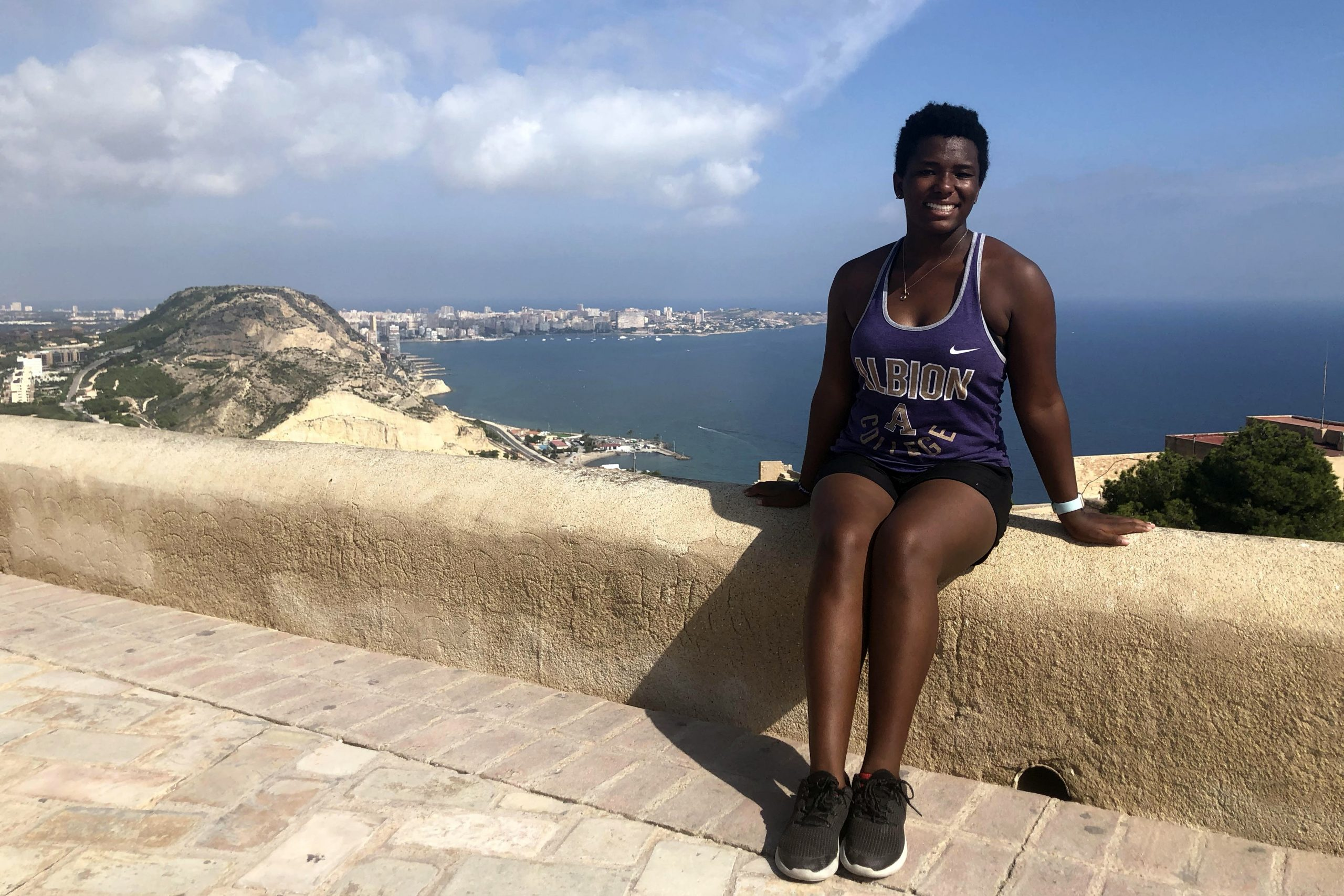 LaRhonda Richardson sitting on a coastal wall in front of the ocean in Spain.