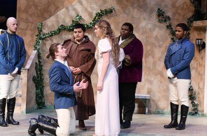 Group of Albion students acting in costume on stage.