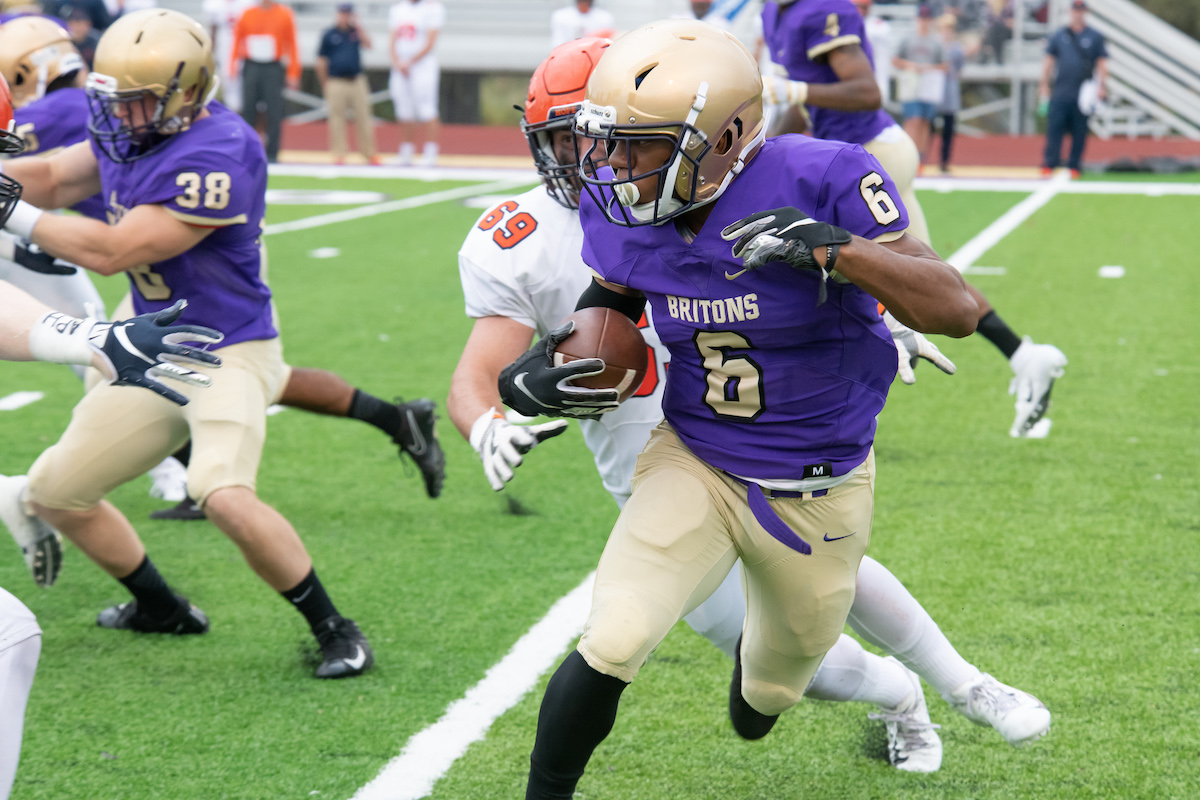 Member of the Albion College football team running with a football during a game.