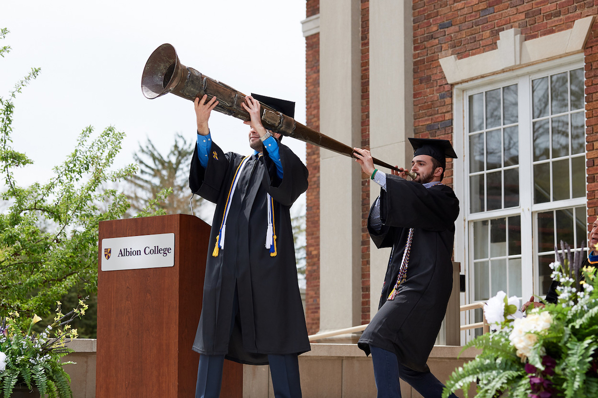 Two students at graduation blowing the senior horn at commencement.