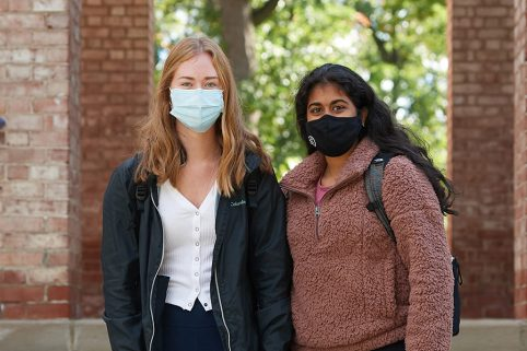 Two students standing outside Baldwin Hall wearing masks.