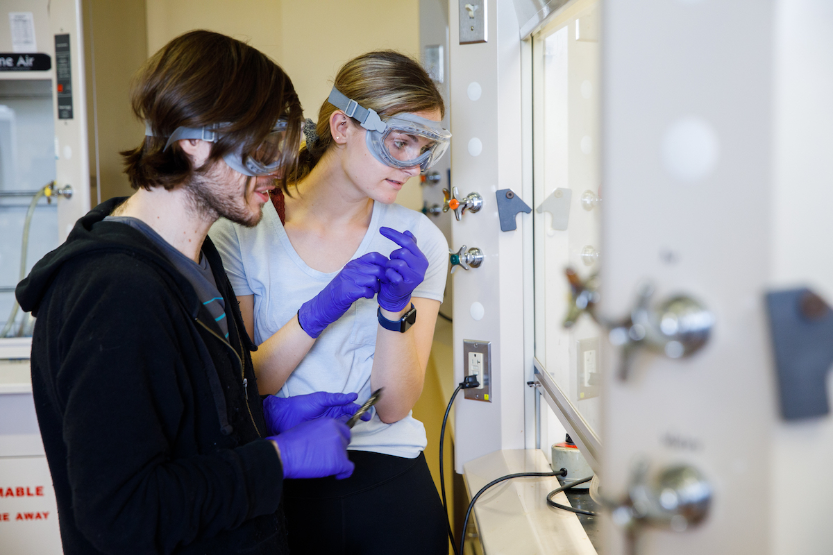 Two students wearing protective goggles in a lab setting.