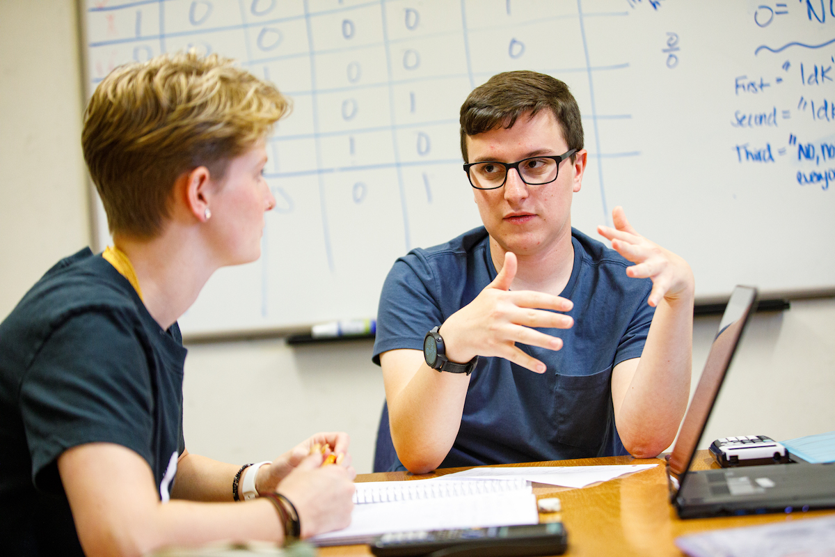 Two students conversing in front of a whiteboard.