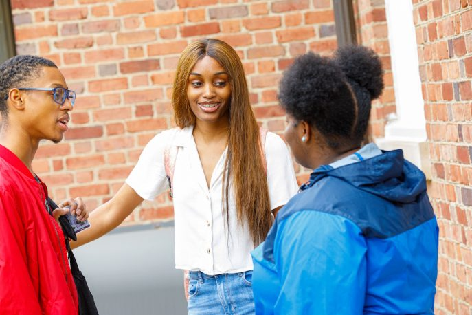 Three Albion students conversing outside of a campus building.
