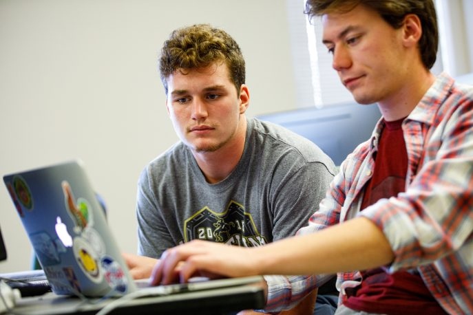 Two students working together on a laptop computer.