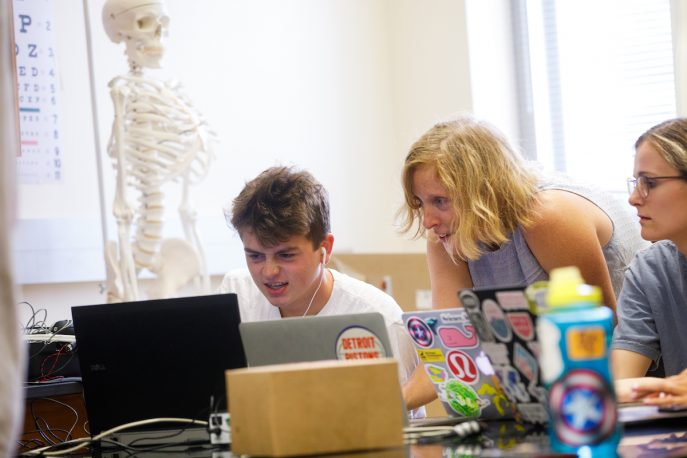 Students on computers in a lab setting, with a model of a skeleton in the background.