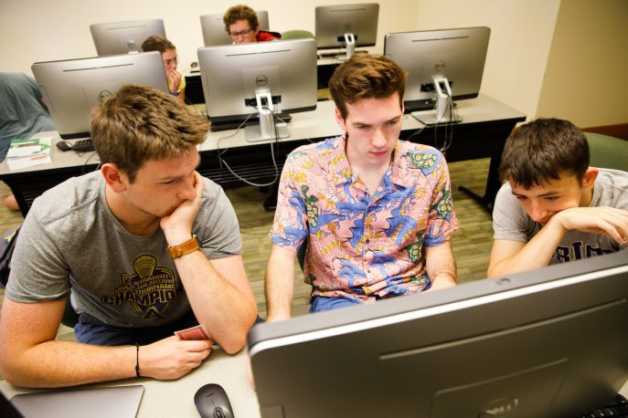 Three students working together in a computer lab.