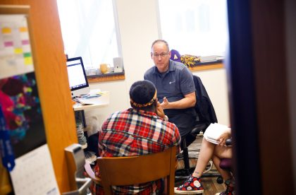 Faculty member conversing with two students in an office.